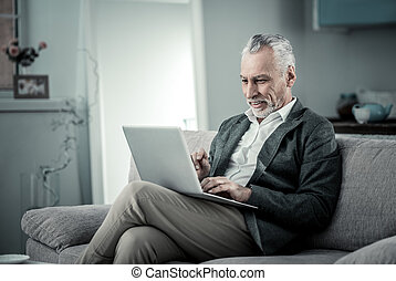 Delighted mature businessman looking at computer