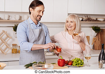 Delighted mature son helping aged mother cooking in the kitchen