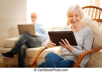Delighted mature woman watching photos