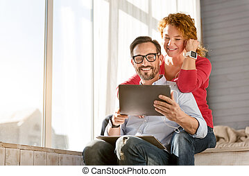 Delighted middle aged couple enjoying the music at home