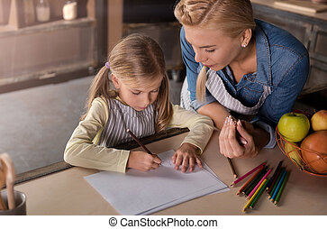 Delighted mother drawing with her daughter in the kitchen