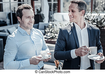 Delighted nice businessmen enjoying their coffee