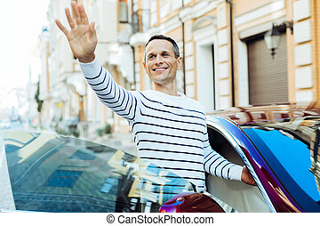Delighted nice man holding his hand up