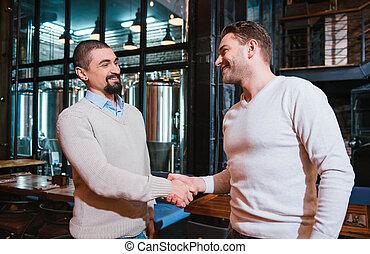 Delighted nice men shaking hands