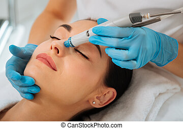 Delighted nice positive woman having hydrafacial procedure