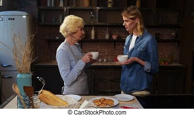 Delighted nice woman drinking tea with her elderly mother
