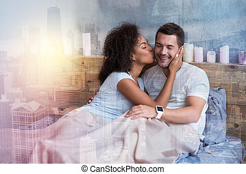 Delighted nice woman kissing her boyfriend