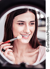 Delighted nice woman using a makeup brush