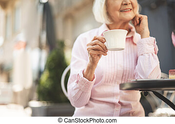 Delighted old lady drinking hot drink outdoors
