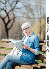 Delighted old woman reading a book