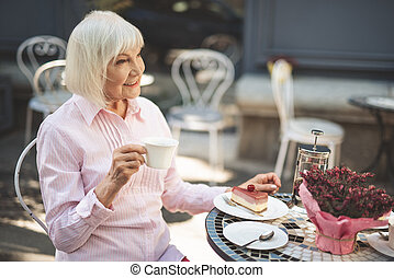 Delighted old woman sitting at table outside