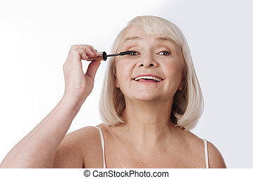 Delighted optimistic woman using a mascara brush