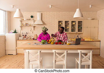 Delighted positive couple cooking food in the kitchen
