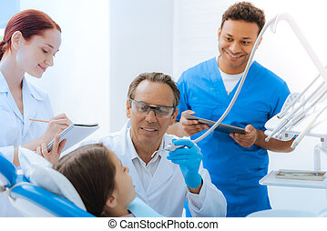 Delighted positive doctor treating his young patient