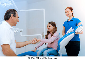 Delighted positive girl greeting her doctor