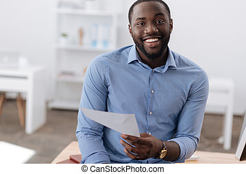 Delighted positive man holding a document