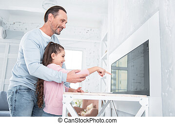 Delighted positive man holding his daughters hand