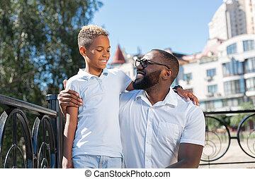 Delighted positive man hugging his beloved son