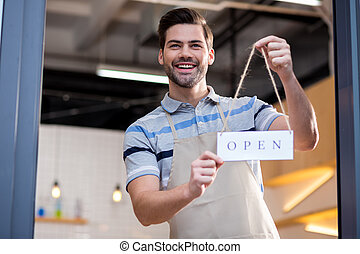 Delighted positive man inviting customers