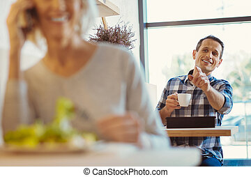 Delighted positive man sitting in the cafe