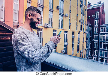 Delighted positive man typing a message to a friend