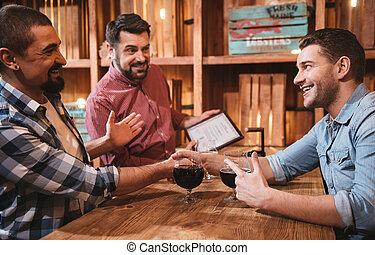 Delighted positive men shaking hands