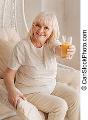 Delighted positive woman offering you orange juice