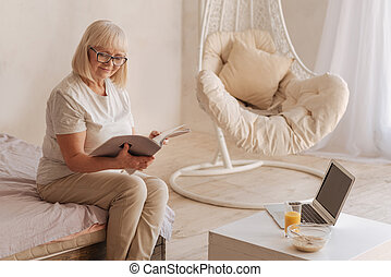 Delighted positive woman reading a magazine