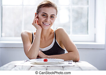 Delighted positive woman sitting at the table