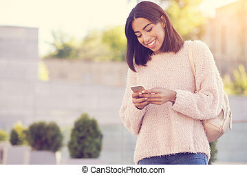 Delighted positive woman using her cell phone
