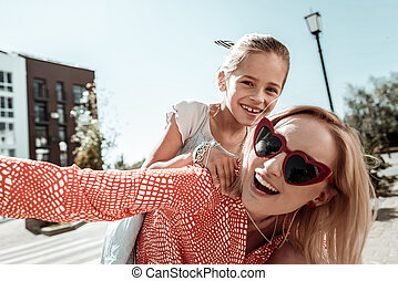 Delighted positive young woman holding her daughter
