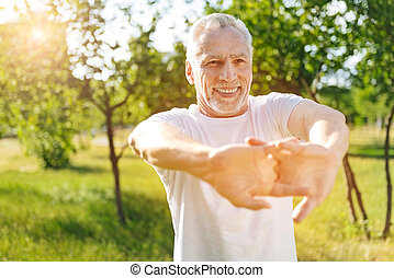 Delighted retired man doing stretching exercises