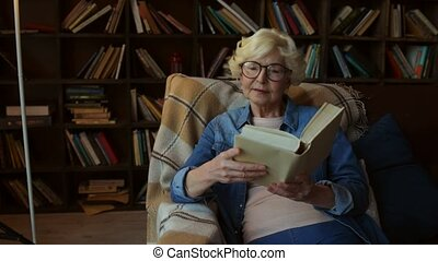 Delighted senior lady reading a book at home