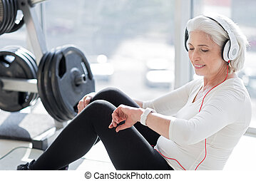 Delighted senior woman enjoying music after workout.