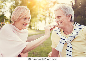 Delighted senior woman holding a cookie