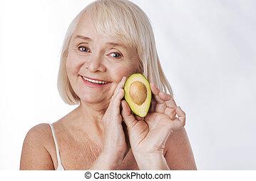 Delighted senior woman holding an avocado