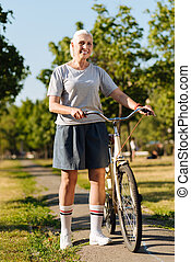 Delighted senior woman standing with her bicycle