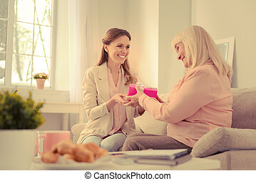 Delighted senior woman taking a gift box