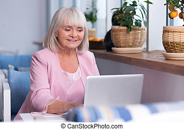 Delighted senior woman working