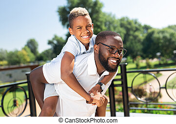 Delighted strong man having fun with his son