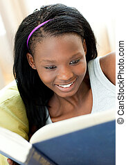 Delighted teen girl studying lying on a sofa