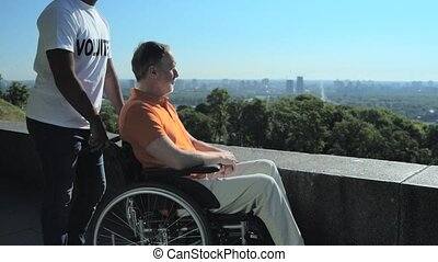 Delighted wheelchaired man enjoying the view over the city -...