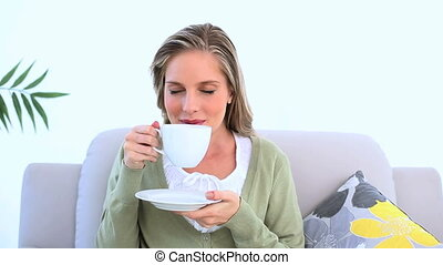Delighted woman drinking a cup of