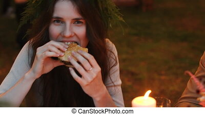 Delighted woman eating hamburger