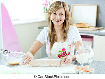 Delighted woman is preparing a cake in the kitchen