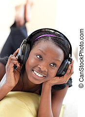 Delighted woman listening music with headphones lying on a sofa