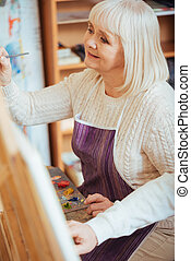 Delighted woman painting on a canvas