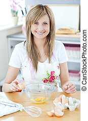 Delighted woman preparing a cake in the kitchen