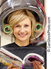 Delighted woman reading a magazine with hair curlers under a hairdryer in a hairdressing salon