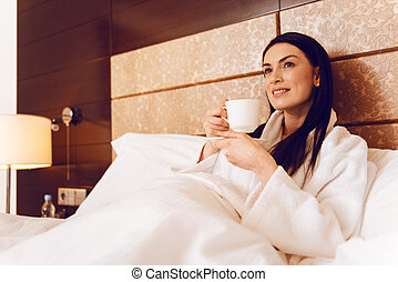 Delighted woman relaxing at hotel room